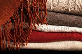 Several woolen sweaters stacked on top of each other and a scarf on top of them poster