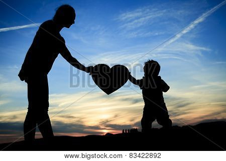 Mother holding baby up in the back lit,