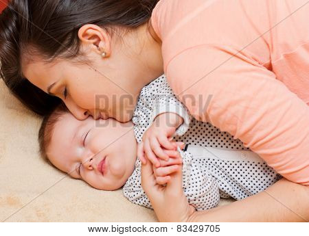 Mother Kissing Sleeping Baby