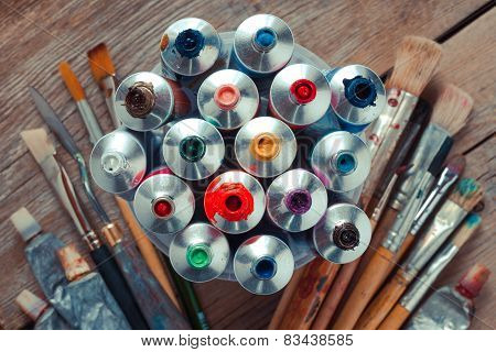 Vintage Stylized Photo Of Oil Multicolor Paint Tubes Closeup And Artist Paintbrushes On Wooden Desk.