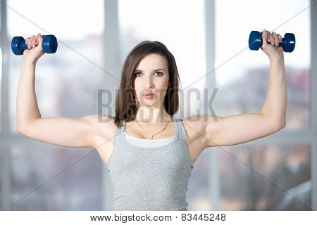 Sporty Young Woman Lifting Dumbbells