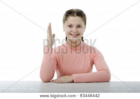 Little Girl At The Table In School On White
