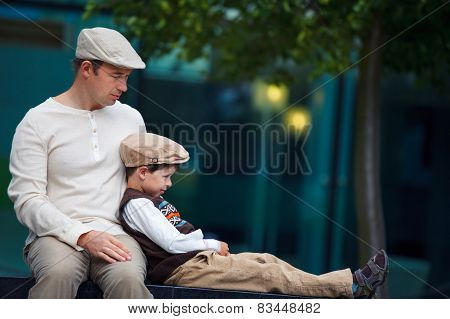 Young father and son having rest outdoors in city