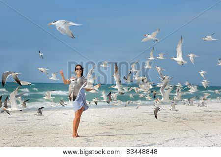 Young beautiful woman watching the seagulls flying
