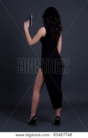 Back View Of Sexy Woman Secret Agent Posing With Gun Over Grey