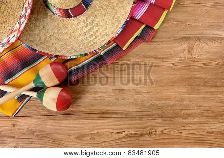 Mexican background with sombrero straw hat maracas and traditional serape blanket or rug on a wood floor. Space for copy. poster