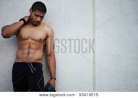 Young man taking break after workout outdoors while standing on background wall at copy space