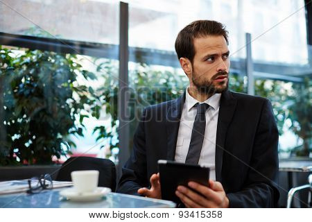 Young successful businessman sitting in an coffee shop and using a digital tablet