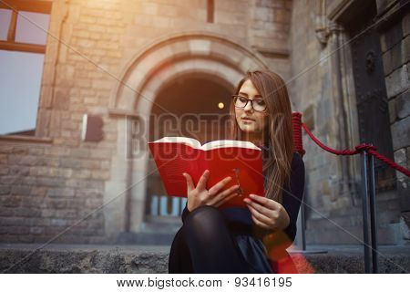 Portrait of a female university student reading interesting book sitting on the stairs