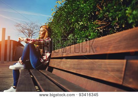 Side view seated woman on the bench relaxed while enjoying nature in sunny day outdoors