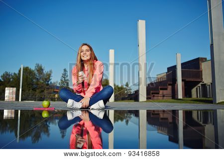 Portrait of young woman holding her smart phone sitting at beautiful park on sunny day