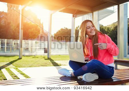 Young beautiful student pointing to open laptop while looking for someone at campus