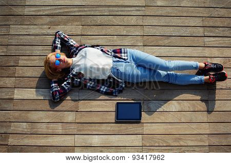 Attractive student lying on the wooden floor with a tablet enjoying the good weather and the sun