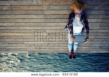 Young stylish girl is lying on the wooden pier after active walking makes self on the touch tablet