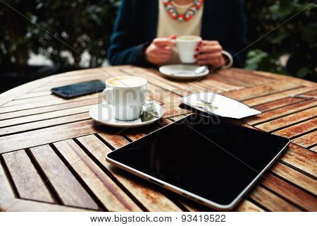 Smart phone digital tablet and coffee on a wooden table with empty chair black touch screen computer