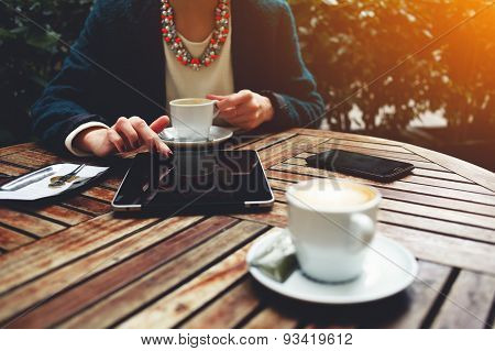 Girl sitting in a cafe on wooden table on which stands a cup of coffe phone and working on a tablet