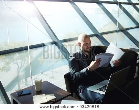 Portrait of elegant business man looking over some paperwork sitting next to big window in office.