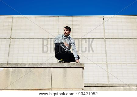 Portrait of a young parkour sitting on the edge of a large house in preparation for the next jump