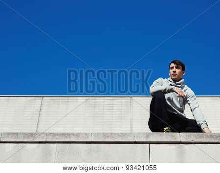 Portrait of a young parkour athlete sits on the roof of a large building and is preparing to jump