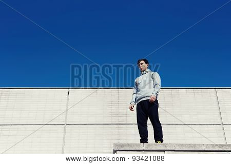 Portreit young parkour standing on the roof on a background of white walls and sky preparing to jump