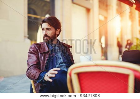 Portrait of handsome and stylish man with beard enjoying a cup of coffee in a coffee shop