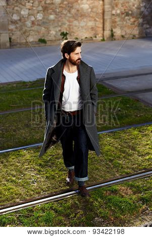 Portrait of young hipster dressed in modern clothes that walking in the warm autumn evening.