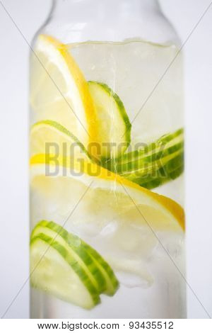 healthy eating, drinks, diet and detox concept - close up of fruit water with lime, lemon and cucumber in glass bottle poster