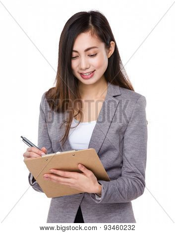 Asian businesswoman jotting note on clipboard