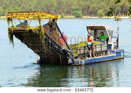 PILSEN CZECH REPUBLIC - JUNE 12, 2015: Unidentified crew with rare underwater harvestor boat Bolek on a Bolevecky rybnik lake harvesting water weed. This machine is only one in Central Europe.