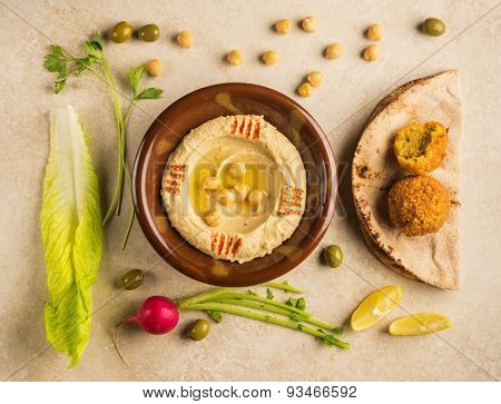 Various food ingredients arranged around bowl of Houmous - a popular Middle Eastern dip. View from top. poster