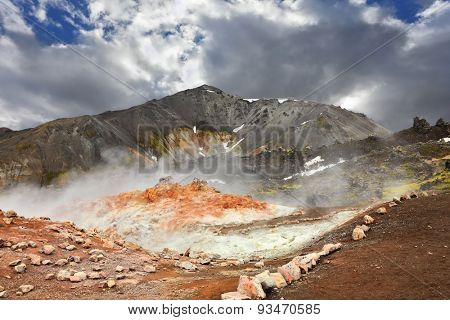 Rhyolite mountains smoldering underground heat. In the hollows lie unmelted snow patches from last year