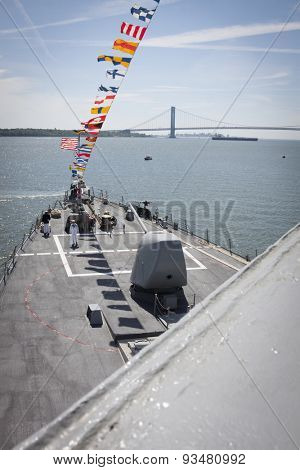 STATEN ISLAND, NY - MAY 24 2015: Navy personnel on deck of the USS Barry (DDG 52) moored at Sullivans Pier in Staten Island with the Verrazano Narrows Bridge in the background during Fleet Week 2015.