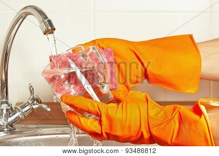 Hands in gloves with sponge wash the glass over the sink in kitchen
