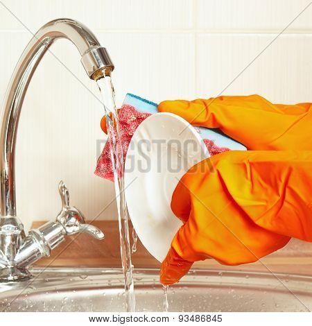 Hands in rubber gloves wash the plate under running water in kitchen