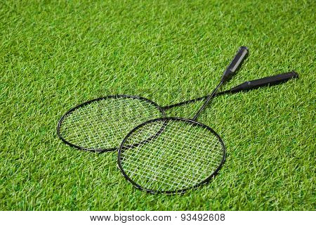 Crossed badminton rackets lying on grass