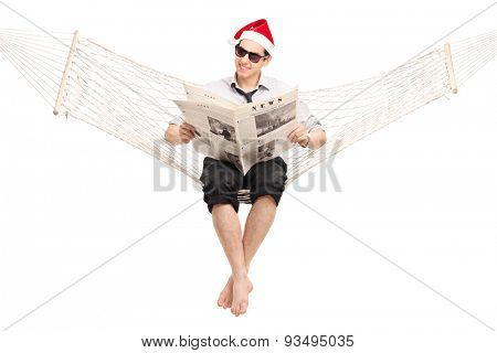 Young guy with Santa hat sitting in a hammock and reading a newspaper. The photos used in the newspaper in my copyright, you can check from the Model release that I am uploading additionally.
