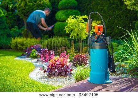 Garden Pest Control Spray and Male Gardener in the Background. Spraying Pesticides in a Garden. Gardening Theme. poster