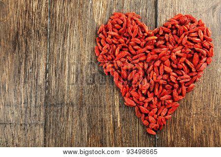 Goji berries arranged in heart shape on wooden background