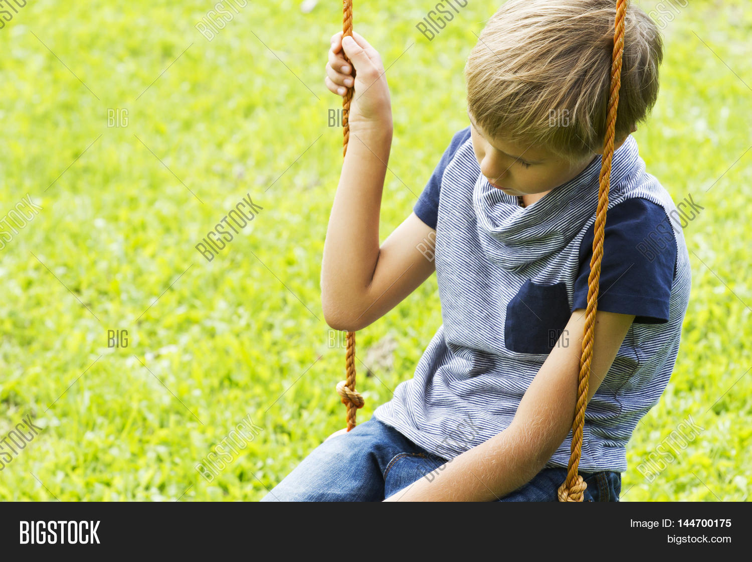 Sad lonely boy sitting on swings at outdoor playground close up sad lonely depressed