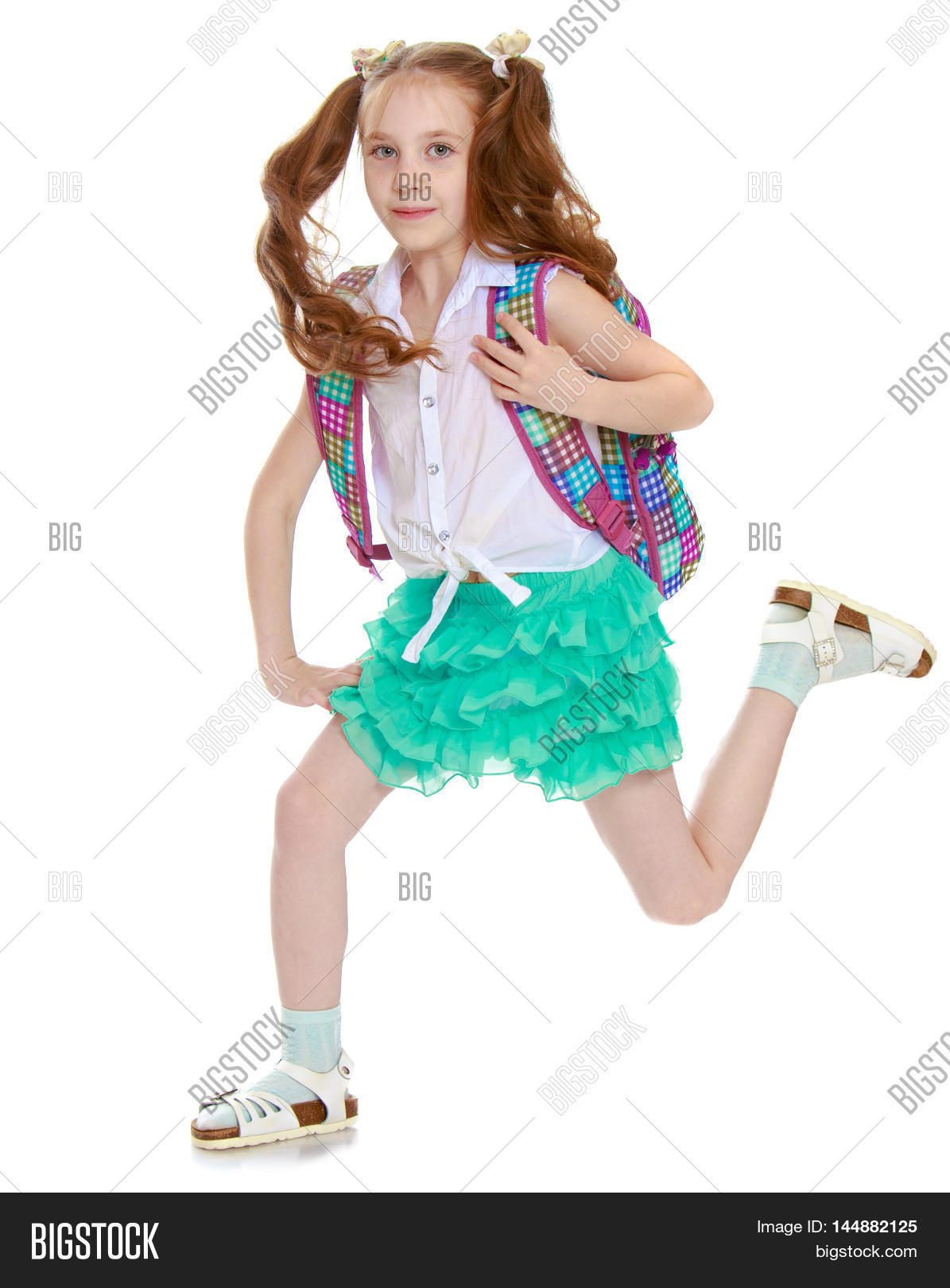 7304c3d01826 Cute little girl in a short green skirt and white shirt with a backpack on  their