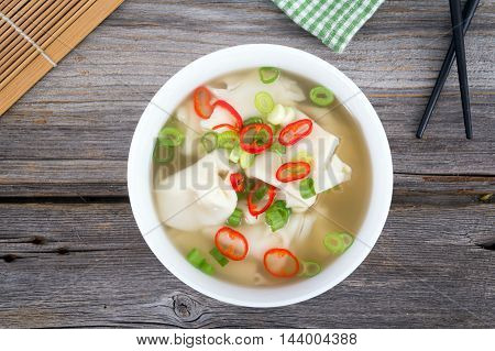 Wonton dumpling asian soup with green onion and thai pepper