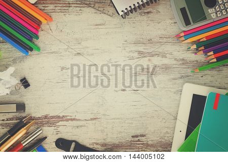 back to school frame with school supplies on aged wooden table, retro toned