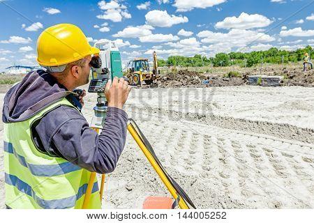 Zrenjanin Vojvodina Serbia - June 22 2015: Surveyor engineer is measuring level on construction site. Surveyors ensure precise measurements before undertaking large construction projects.