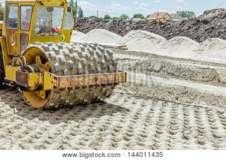 Construction worker is driving huge road roller with spikes and compacting soil for a large foundation. poster