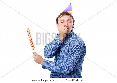 the concept of a sweet tooth isolated on white background. young man in a birthday party hat holding a lollipop. guy closed his eyes with pleasure and smiles in anticipation of eating sweets