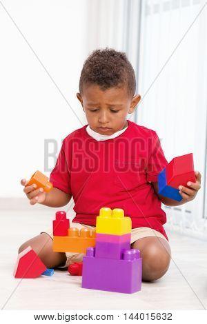 Little cute preschool boy play construction set
