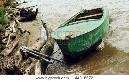 Old Green Boat With Oars On The Coast