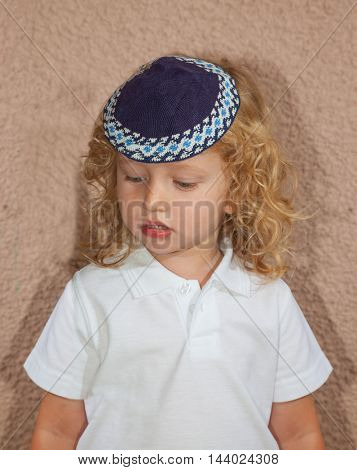 Adorable child in a blue skullcap. Little boy with long blond curls and blue eyes