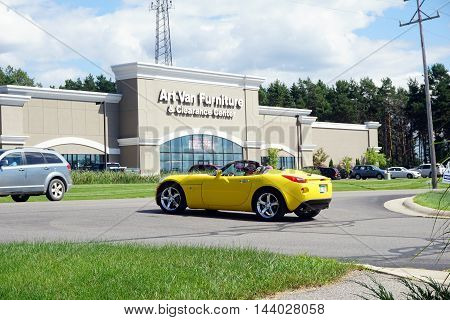 PETOSKEY, MICHIGAN / UNITED STATES - AUGUST 1, 2016: The driver of a yellow Pontiac solstice waits to make a left turn onto Anderson Road, in front of the Art Van Furniture and Clearance Center.