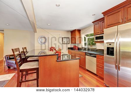 Wooden Kitchen Interior With Kitchen Island And Steel Appliances